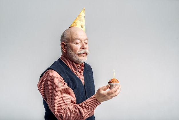 Lächelnder älterer mann in der parteimütze zeigt kuchen mit kerze. fröhlicher reifer senior
