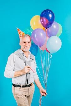 Lächelnder älterer mann mit den ballonen und partyhorn, die kamera auf blauem hintergrund betrachten
