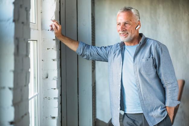 Lächelnder älterer mann mit drahtlosem bluetooth, das fenster betrachtet