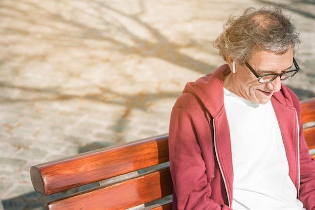 Lächelnder älterer mann mit drahtlosem kopfhörer auf seinem ohr, das auf bank sitzt