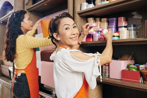 Lächelnder älterer vietnamesischer florist, der bunte satinbandspulen auf regal im blumenladen anordnet