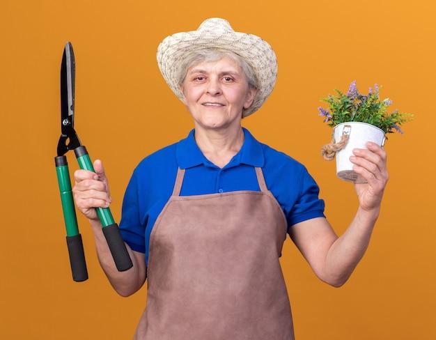 Lächelnder älterer weiblicher gärtner, der gartenhut trägt, der gartenschere und blumentopf auf orange hält
