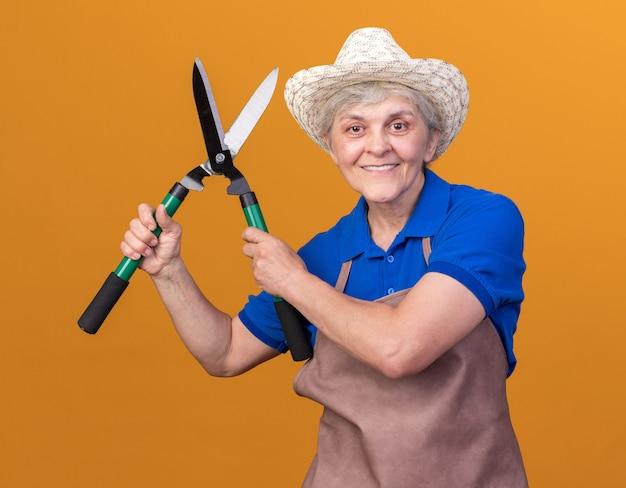 Lächelnder älterer weiblicher gärtner, der gartenhut trägt, hält gartenschere auf orange