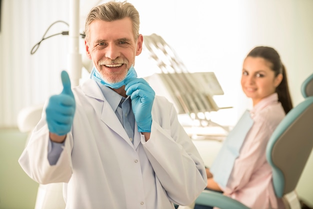 Lächelnder älterer zahnarzt, der sich daumen zeigt.
