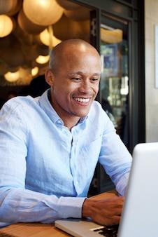 Lächelnder afrikanischer geschäftsmann, der an laptop arbeitet
