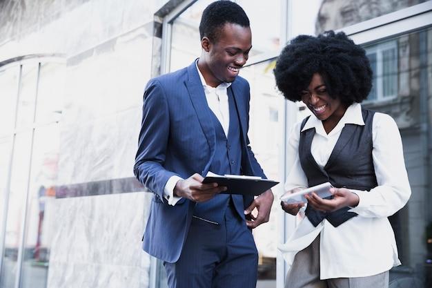 Lächelnder afrikanischer junger geschäftsmann und geschäftsfrau, die klemmbrett und digitale tablette hält