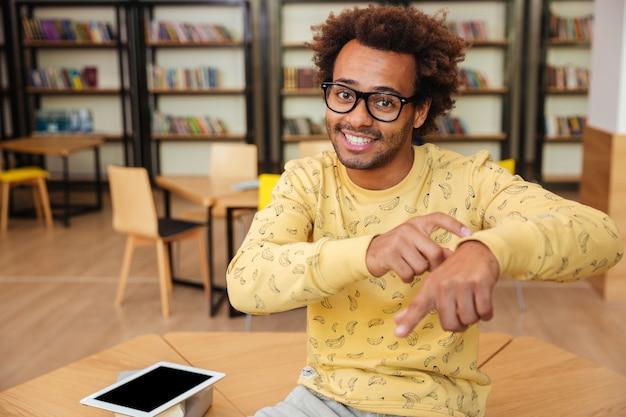 Lächelnder afrikanischer junger mann, der tablet benutzt und nach der zeit in der bibliothek fragt