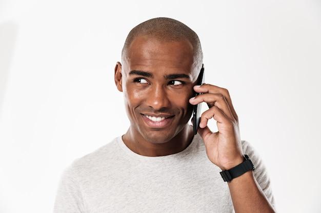 Lächelnder afrikanischer mann, der durch das smartphone spricht und wegschaut