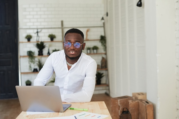 Lächelnder afrikanischer mann, der in einem modernen büro hinter einem laptop arbeitet und in die kamera schaut
