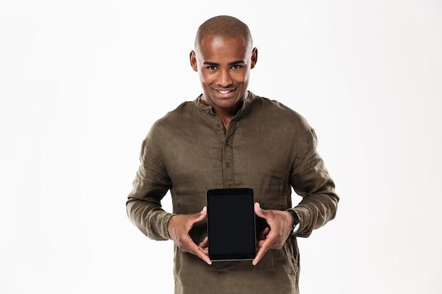 Lächelnder afrikanischer mann, der leeren tablet-computerbildschirm zeigt und schaut