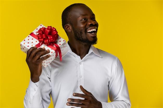 Lächelnder afrikanischer mann, der weg schaut und eine geschenkbox hält