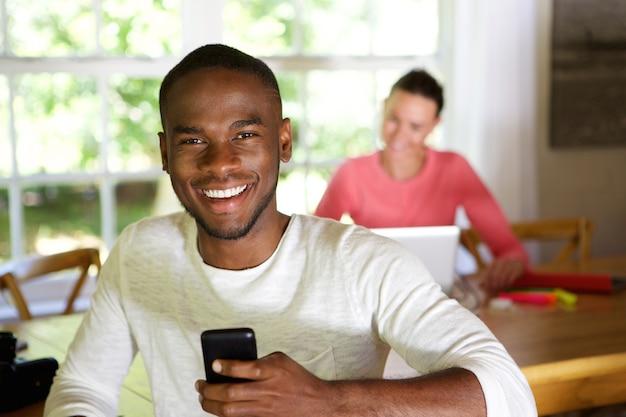 Lächelnder afrikanischer mann zu hause mit der frau, die laptop im hintergrund verwendet