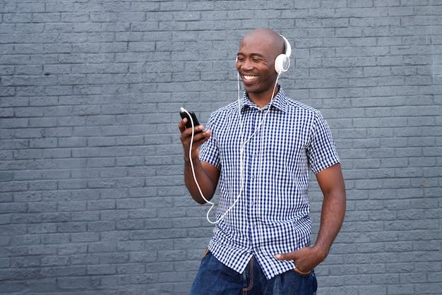Lächelnder afroamerikaner mit kopfhörern und intelligentem telefon