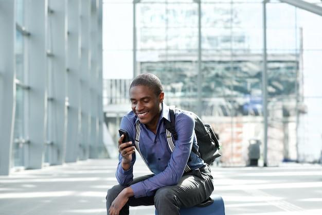 Lächelnder afroamerikanergeschäftsmann, der an der station wartet