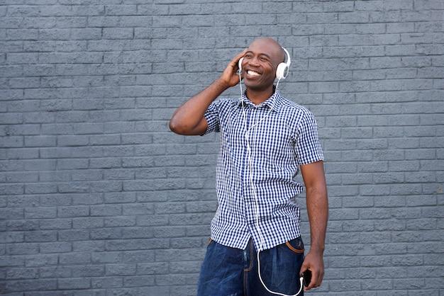 Lächelnder afroamerikanerkerl, der musik auf kopfhörern hört