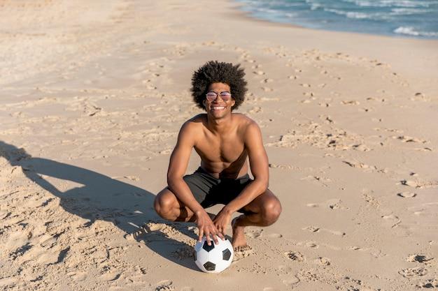 Lächelnder afroamerikanermann, der mit ball auf sommerstrand sitzt