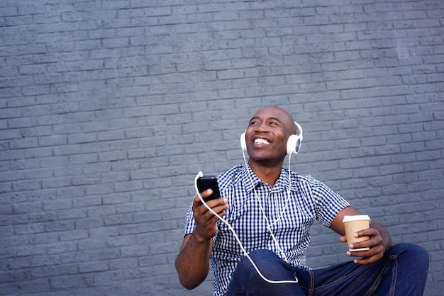 Lächelnder afroamerikanermann, der musik auf kopfhörern hört