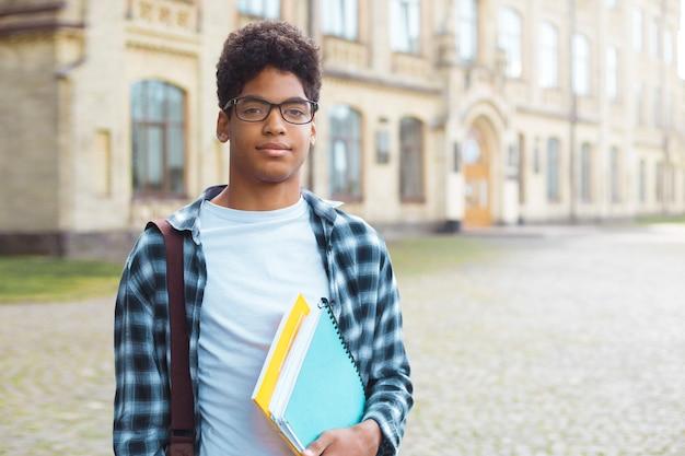 Lächelnder afroamerikanerstudent mit gläsern und mit büchern nähern sich college. porträt eines glücklichen schwarzen jungen mannes, der auf einer universität steht