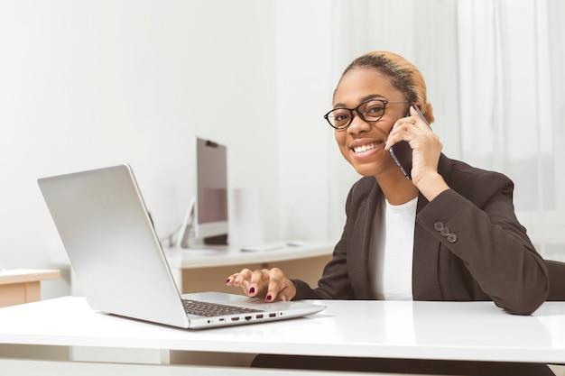 Lächelnder afroamerikanischer geschäftsfrauenmanager, der am telefon spricht, während er am arbeitsplatz sitzt.