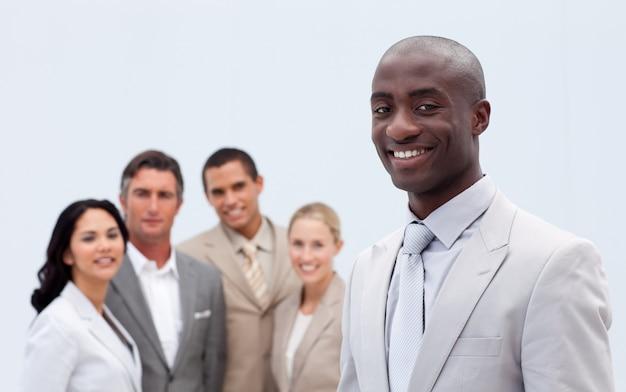 Lächelnder afroamerikanischer geschäftsmann vor seinem team