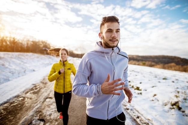 Lächelnder aktiver mann in der wintersportbekleidung mit kopfhörern, die mit einem lächelnden mädchen mit einem pferdeschwanz draußen im schnee laufen