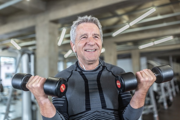 Lächelnder alter mann trainiert mit hanteln in einem fitnessstudio.