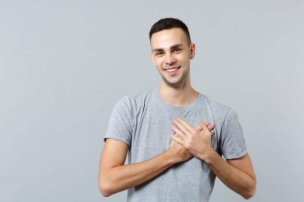 Lächelnder angenehmer junger mann in freizeitkleidung, der die handflächen auf der herzbrust gekreuzt hält