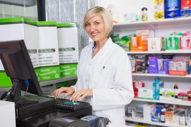 Lächelnder apotheker, der computer in der apotheke verwendet