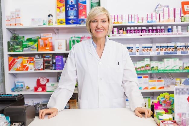 Lächelnder apotheker, der hinter dem zähler aufwirft