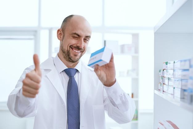 Lächelnder apotheker hält eine schachtel mit medikamenten und zeigt einen daumen nach oben