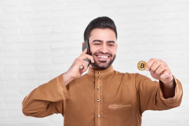 Lächelnder arabischer geschäftsmann hält goldenes bitcoin.