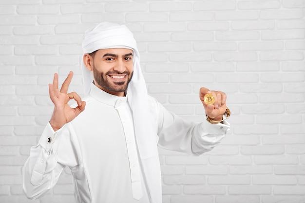 Lächelnder arabischer mann hält bitcoin und schaut sehr glücklich und steht auf weißem hintergrund.
