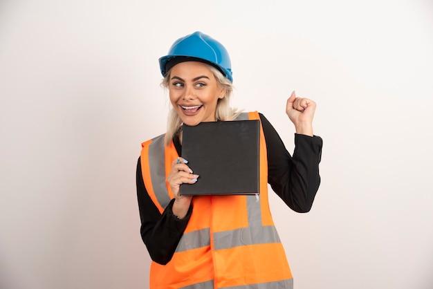 Lächelnder arbeiter mit notizbuch, das auf weißem hintergrund steht. hochwertiges foto