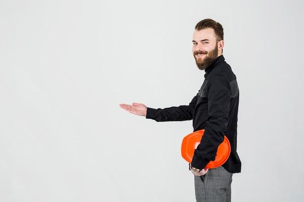 Lächelnder architekt, der den hellen hardhat sich darstellt gegen weißen hintergrund hält