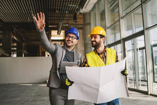 Lächelnder architekt, der tablette hält und dem bauarbeiter etwas zeigt, das er sich vorstellte. bauarbeiter, der blaupausen hält. innenraum der baustelle.