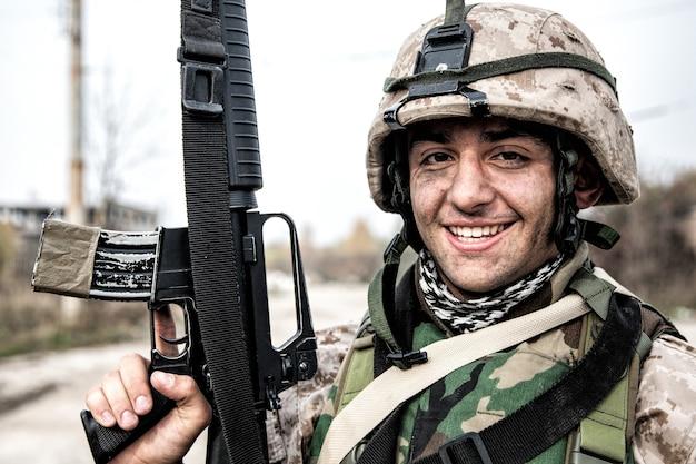 Lächelnder armeesoldat, infanterie-schütze des united states marine corps in camo-kampfuniform, geschützt mit körperpanzer und helm, posiert mit sturmgewehr in den händen, während er in der nähe der landstraße steht standing
