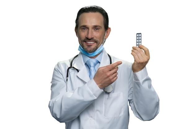 Lächelnder arzt, der die blisterpackung tabletten hält. erfahrener arzt zeigte auf das mittel. reifer apotheker lokalisiert auf weißer wand.