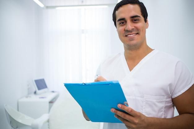 Lächelnder arzt, der eine medizinische akte in der klinik hält