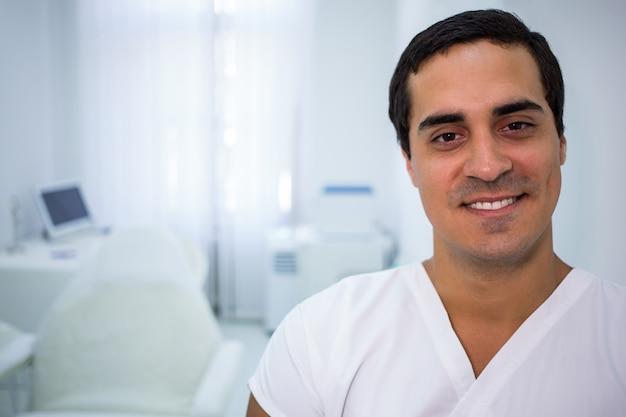 Lächelnder arzt, der in einer klinik steht