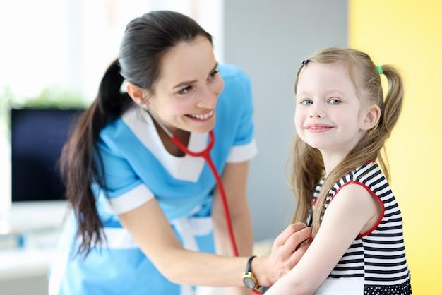 Lächelnder arzt hört mit stethoskop auf die atmung des kleinen mädchens