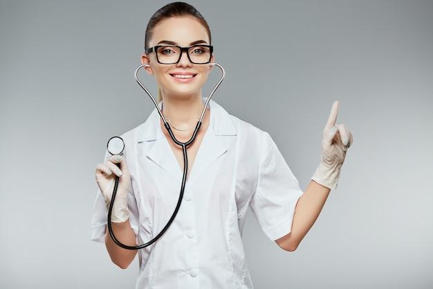 Lächelnder arzt mit braunen haaren und nacktem make-up trägt weiße medizinische uniform, brille, stethoskope und weiße handschuhe am grauen studiohintergrund, porträt, zeigt mit dem finger.