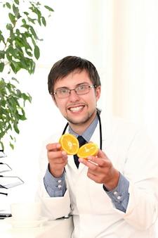 Lächelnder arzt mit orange in den händen