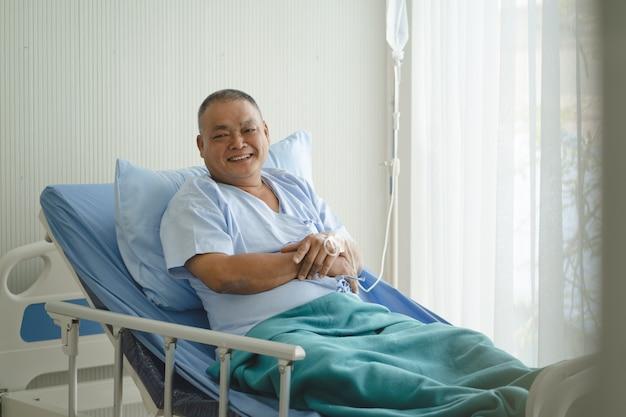 Lächelnder asiatischer älterer mann auf dem bett im krankenhaus