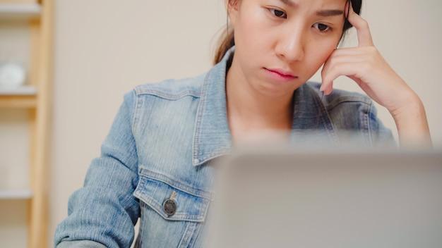 Lächelnder asiatischer frauenarbeitslaptop der schönen junge auf schreibtisch im wohnzimmer zu hause. asien-geschäftsfrau, die notizbuchdokumentenfinanzierung und -rechner im innenministerium schreibt.