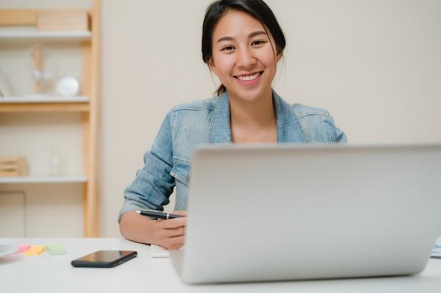 Lächelnder asiatischer frauenarbeitslaptop der schönen junge auf schreibtisch im wohnzimmer zu hause.