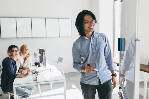 Lächelnder asiatischer freiberuflicher entwickler, der aktionsplan des flipcharts zeichnet. blonde junge managerinnen, die ausländische kollegin betrachten, die etwas an bord schreibt.