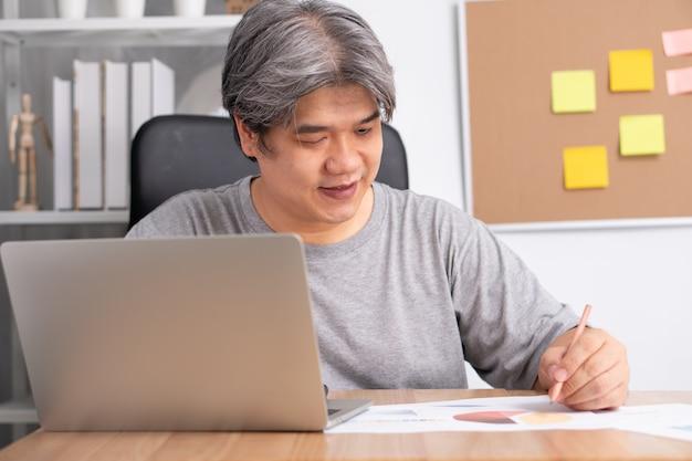 Lächelnder asiatischer geschäftsmann, der am computer arbeitet und notiz auf notizbuch nimmt