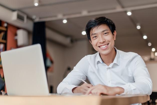 Lächelnder asiatischer geschäftsmann im firmenbüro mit laptop