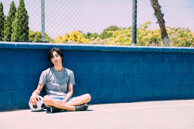 Lächelnder asiatischer jugendlich student, der mit fußball sich entspannt