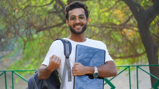 Lächelnder asiatischer junger mann mit dem glücklichen mannbild des laptops - online-bildungskonzept